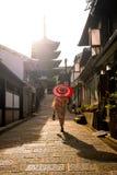 Fille japonaise dans Yukata avec le parapluie rouge dans la vieille ville Kyoto Photos libres de droits
