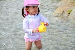 Fille japonaise jouant avec de l'eau avec le pot d'arrosage Photographie stock libre de droits