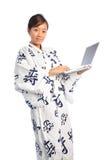 Fille japonaise utilisant un sourire d'ordinateur portatif heureux Photos libres de droits