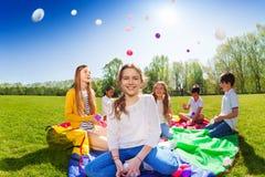 Fille jetant les boules colorées jouant avec des amis Image libre de droits