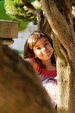 Fille jetant un coup d'oeil autour de l'arbre Image stock
