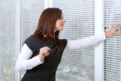 Fille jetant un coup d'oeil par des abat-jour de fenêtre sur la rue Images libres de droits