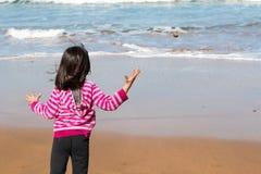 Fille jetant un rocher dans la mer Images libres de droits