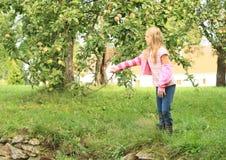 Fille jetant une pomme Photographie stock