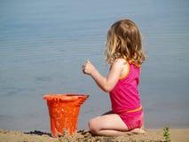 Fille jouant à la plage Photo stock