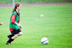 Fille jouant au football Image stock