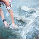 Fille jouant avec de l'eau en mer images libres de droits