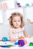 Fille jouant avec de la pâte à modeler colorée Photographie stock libre de droits
