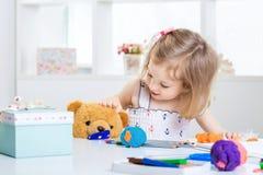 Fille jouant avec de la pâte à modeler colorée Image libre de droits