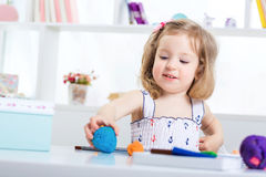 Fille jouant avec de la pâte à modeler colorée Photo stock