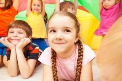 Fille jouant avec des amis se cachant sous le parachute Images libres de droits