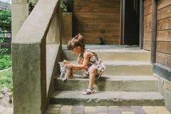 Fille jouant avec des chatons sur la terrasse Images stock