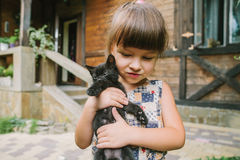 Fille jouant avec des chatons sur la terrasse Photo libre de droits