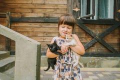 Fille jouant avec des chatons sur la terrasse Images libres de droits