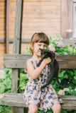 Fille jouant avec des chatons sur un banc Photo libre de droits