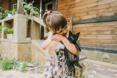 Fille jouant avec des chatons sur un banc Photographie stock libre de droits