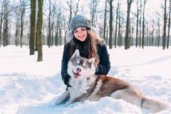 Fille jouant avec des chiens dans la neige Photo stock