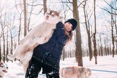Fille jouant avec des chiens dans la neige Photos stock