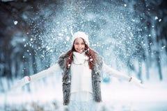 Fille jouant avec la neige en parc Image stock