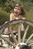 Fille jouant avec la roue de chariot Images stock