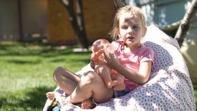 Fille jouant avec le bébé - poupée dans l'arrière-cour banque de vidéos