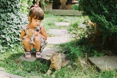 Fille jouant avec le chat de chatons Photos libres de droits
