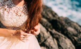 Fille jouant avec le cheveu La jeune mariée rouge joue avec des boucles sur le RO Photos libres de droits