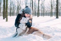 Fille jouant avec le crabot dans la neige Image stock