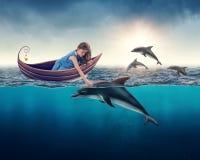 Fille jouant avec le dauphin images libres de droits