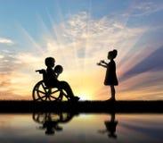 Fille jouant avec le garçon handicapé avec le jour de boule Photographie stock libre de droits