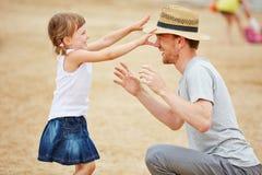 Fille jouant avec le père sur la plage images libres de droits