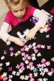 Fille jouant avec le puzzle denteux Photo stock
