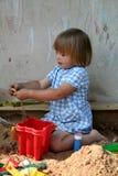 Fille jouant avec le sable Image stock