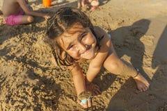 Fille jouant avec le sable dans le bord de la mer de la plage Été Photographie stock