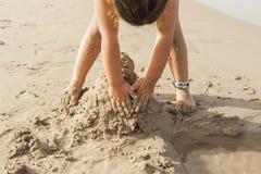 Fille jouant avec le sable dans le bord de la mer de la plage Été Photos stock