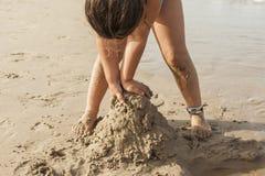 Fille jouant avec le sable dans le bord de la mer de la plage Été Images stock
