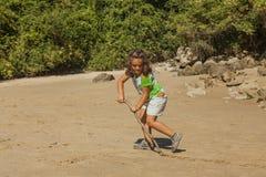 Fille jouant avec le sable dans une plage rocheuse photo stock