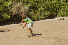 Fille jouant avec le sable dans une plage rocheuse Photographie stock