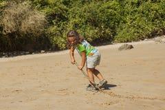 Fille jouant avec le sable dans une plage rocheuse photos stock