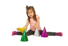 Fille jouant avec les cônes de papier colorés Image stock