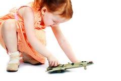 Fille jouant avec un avion de jouet Photographie stock