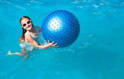 Fille jouant avec une boule bleue Photos stock
