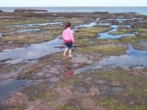 Fille jouant dans des regroupements de roche Images stock