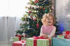 Fille jouant dans la chambre avec un arbre de Noël Photographie stock