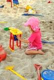 Fille jouant dans la piqûre de sable Images libres de droits