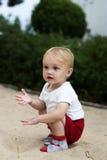 Fille jouant dans le bac à sable Images stock
