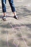 Fille jouant dans le jeu de marelle dehors Image libre de droits