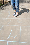 Fille jouant dans le jeu de marelle sur l'allée urbaine Images stock