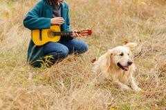 Fille jouant la guitare à côté du chien d'arrêt photos libres de droits