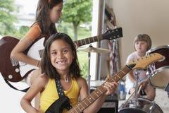 Fille jouant la guitare avec la bande dans le garage Image stock